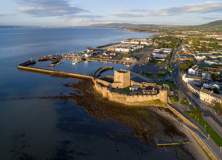 Medieval Norman Castle in Carrickfergus near Belfast in sunrise light. Aerial view with marina, yachts, parking, breakwater, groyne, sediments and far view of Belfast in the background