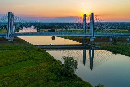 New modern double cable-stayed bridge over Vistula River in Krakow, Poland and its reflection in water at sunset. Part of the ring road around Krakow. Aerial view. Krakow city in the background Zdjęcie Seryjne