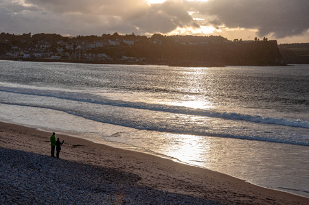 Ballycastle, Northern Ireland, UK. Atlantic coast. Beach, waves and unrecognizable pair in sunset light reflection with dark heavy clouds