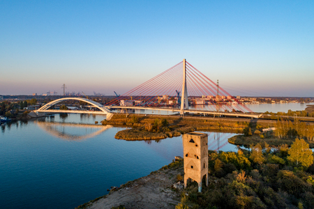 Gdansk, Poland. Modern highway cable-stayed bridge, railway suspension  bridge over Dead Vistula river and old Bartos Tower (Wieża Bartosa). Aerial view. Sunset light. Northern Port in the background
