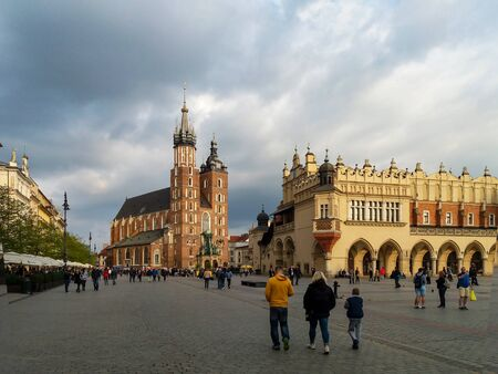 Krakow, Poland – May 7, 2017: Main Market Square (Rynek), Gothic St Mary Church (Mariacki), old drapers' hall (Sukiennice) and walking people. Weather with dark clouds but the sunlight on the church. Publikacyjne