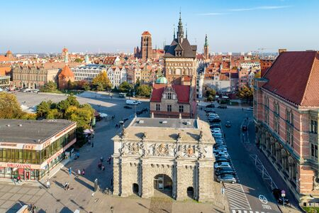 Gdansk, Poland - October 17, 2018: Old city with Renaissance Gate, called Brama Wyzynna  (Upland or High Gate), Prison Gate,  St Mary church and  town hall tower.  Aerial view in sunset light