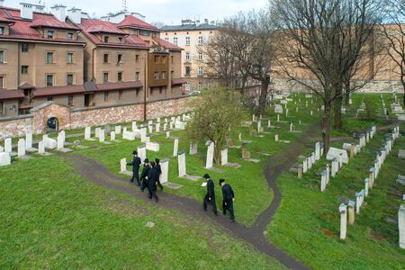 Krakow, Poland - April 11, 2018: A group of orthodox Jews in black visiting Remuh cemetery at still active Remah Synagogue in old historical Jewish Kazimierz (Kazmir) district of Cracow. Aerial view Publikacyjne