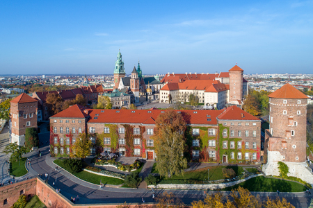 Royal Wawel Gothic Cathedral in Cracow, Poland, with Renaissance Sigismund Chapel with golden dome, Wawel Castle, yard, park and tourists. Aerial view in sunset light