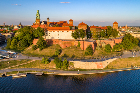 Royal Wawel Cathedral and castle in Krakow, Poland. Aerial view in sunset light. Vistula River, riverbank with park. promenade and  walking people. Old city and Kazimierz district in the background