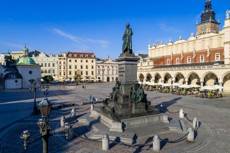 Bronze statue of Adam Mickiewicz, Polish national romantic poet and dramatist on Main Market Square in Krakow, Poland. Monument unveiled in 1898. St. Adalbert church and Sukiennice (Drapers' hall