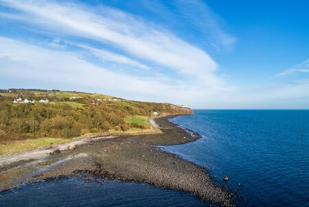 Atlantic coast at the entrance to the Belfast Laugh in County Antrim, Northern Ireland. Far view of Blackhead Lighthouse on a steep cliff. Aerial view. Low tide in winter
