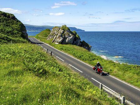 The eastern coast of Northern Ireland and Antrim Coast Road A2, a.k.a Causeway Coastal Route with a motorcycle. One of the most scenic coastal roads in Europe