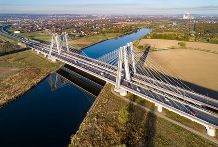 New modern double cable-stayed bridge with wide three-lane roads over Vistula River in Krakow, Poland, and its reflection in water at sunrise. Part of the ring road around Krakow. Aerial view