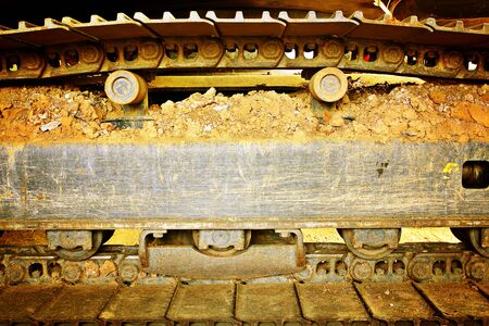 trenching: Technology, transportation, construction. Close-up wheel excavator. Frozen ground,dirty rail.