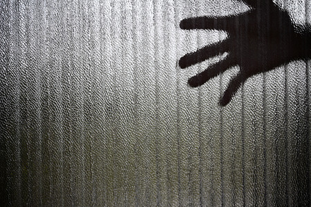 imprisoned: Silhouette of a hand the expression to be imprisoned, blur