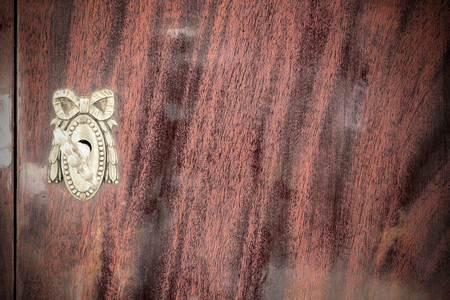 key cabinet: Vintage keyhole with key on vintage wooden cabinet Stock Photo