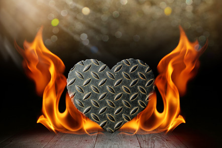 Heart shape steel with blaze fire flame on wooden deck table with bokeh Stock Photo