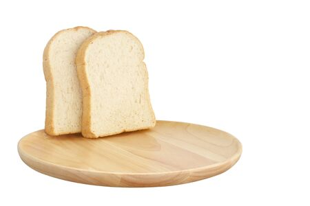 Slice of brown bread on wooden breadboard isolated white background