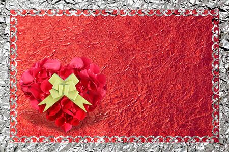 heart shape made out of rose petals with gold bow on red foil background.