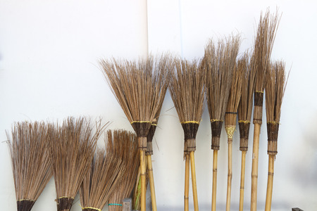 brooms make with coconut leaves on white wall