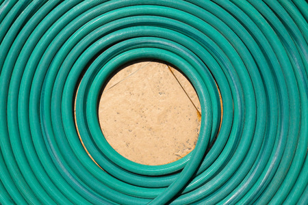 Top view of a green garden hose for background