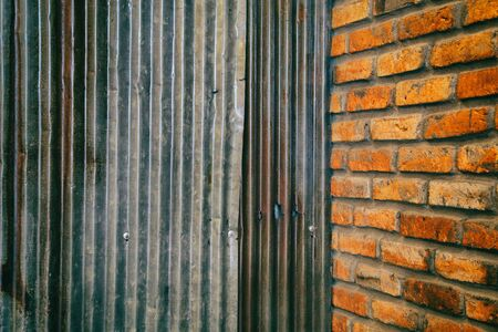 Rusted galvanized iron plate wall and Red brick wall for background 写真素材