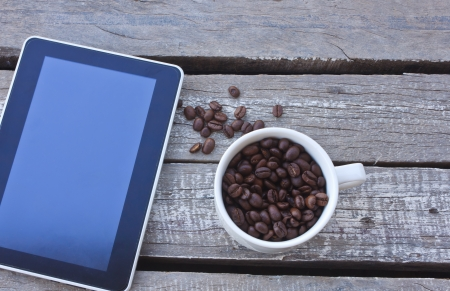 Coffee beans and tablet on wood  photo