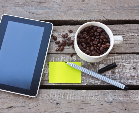 Coffee beans and tablet on wood background photo