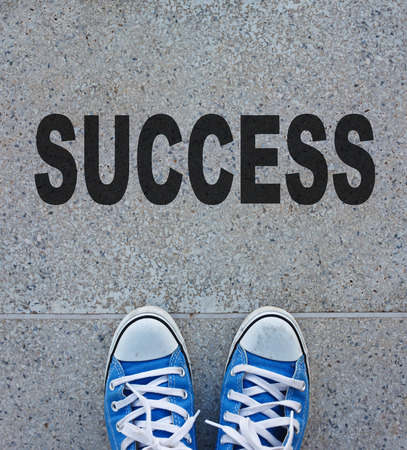 Pair of shoes standing on a road with SUCCESS photo