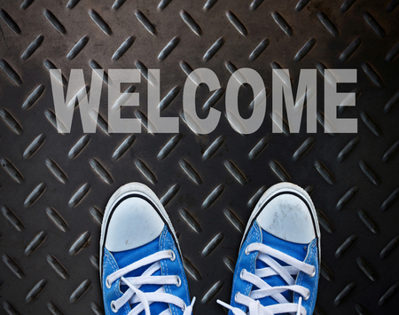 Pair of shoes standing on walkway with WELCOME photo