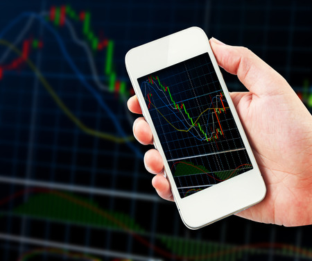 hand holding cellphone with stock exchange screen. photo