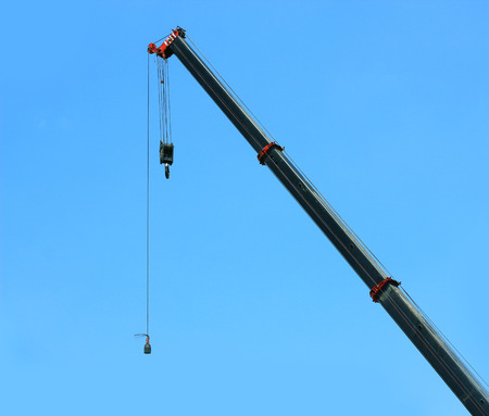 maneuverable: automobile crane with risen telescopic boom outdoors over blue sky Stock Photo