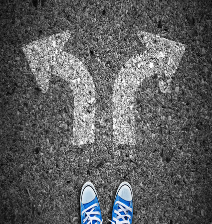 pair of feet standing on road with white arrows Reklamní fotografie