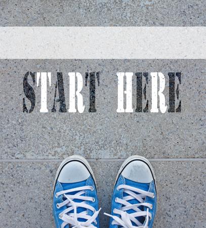Zwarte schoenen die achter de gele lijn en start hier teken Stockfoto