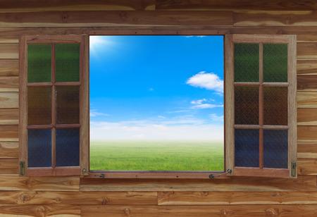 open window: Open window with green field under blue sky on a background Stock Photo