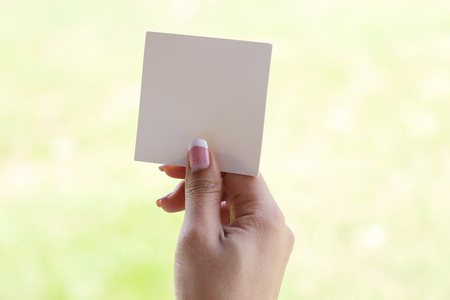 hand holding a piece of blank torn paper on grass background Banco de Imagens