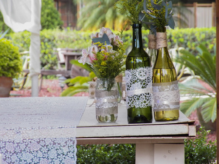Decorated glass bottles as vases on garden table.