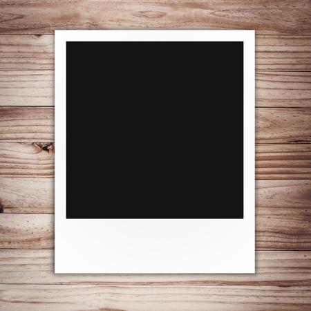 blank Polaroid photo frame on brown wood plank background