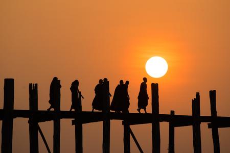 silhouetted: Silhouetted people on U Bein Bridge at sunset, Amarapura, Mandalay region, Myanmar