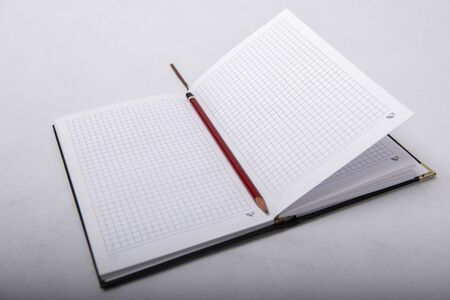 Notepad and pencil stand together on white background Archivio Fotografico