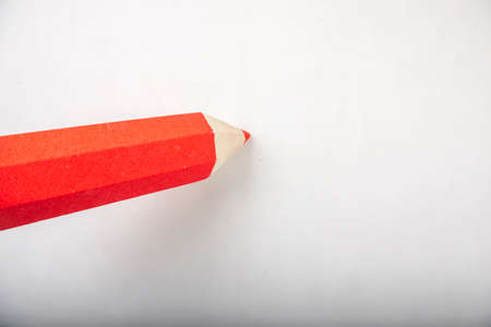 Red pencil stands on a white background.