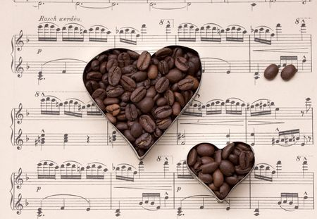 Hearts of Coffee Beans set on old sheet music papers, Still Life photo