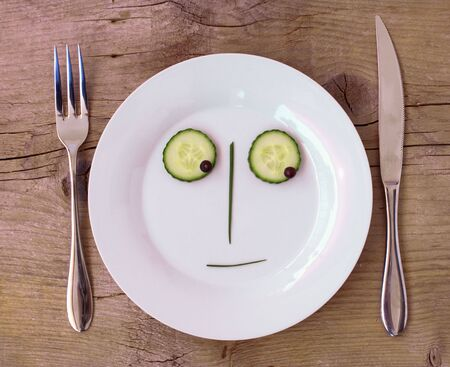 sceptical: Vegetable Face on Plate with knife and fork, set on wooden board - Male, Sceptical Stock Photo