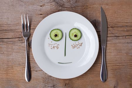 Vegetable Face on Plate with knife and fork, set on wooden board - Male, Surprised photo