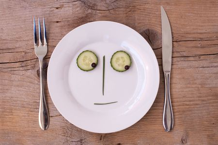 neutral face: Vegetable Face on Plate with knife and fork, set on wooden board - Male, Neutral, looking down