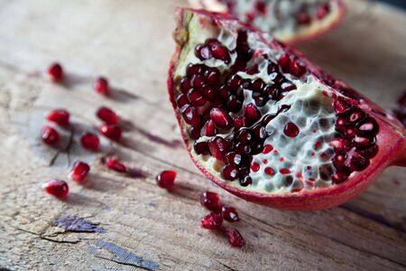 Pomegranate with arils on brown wooden board photo