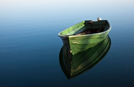 row boat: Single Row boat on Lake with Reflection in the Water Stock Photo