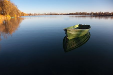 river bank: Single Row boat on Lake with Reflection in the Water Stock Photo