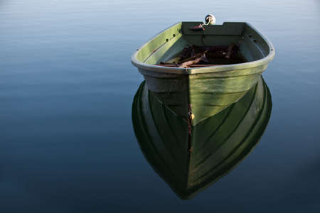 Single Row boat on Lake with Reflection in the Water photo