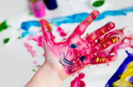 Little Children Hands doing Fingerpainting with vivid colors Stock Photo
