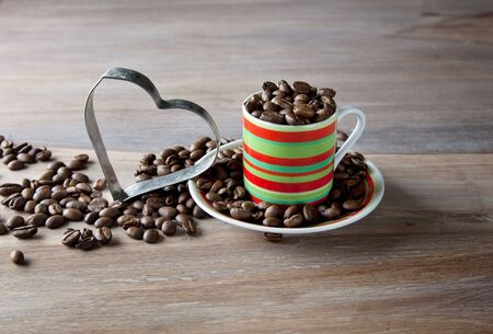 Coffee beans in striped cup with heart on wooden table photo
