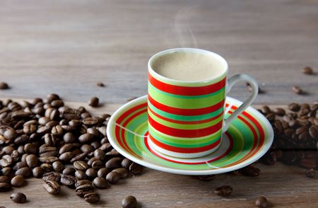 Hot Coffee in striped cup with beans on wooden table photo