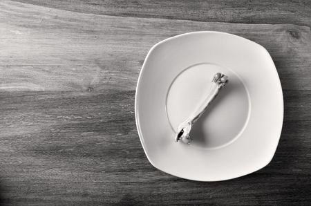 Empty dinner plate with bones set on wooden table Stock Photo - 6534618