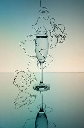 Champagne Glass on mirror surface with wire in soft colors photo